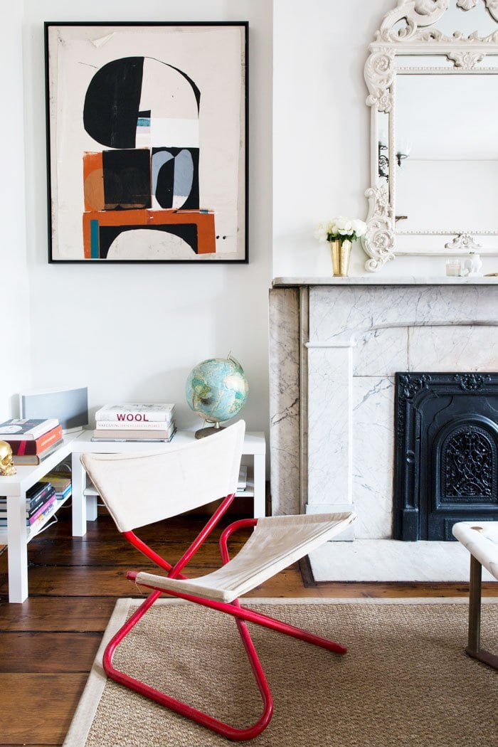 Eclectic living room with canvas chair and marble fireplace mantel in Robert McKinley's Chelsea apartment on Thou Swell @thouswellblog