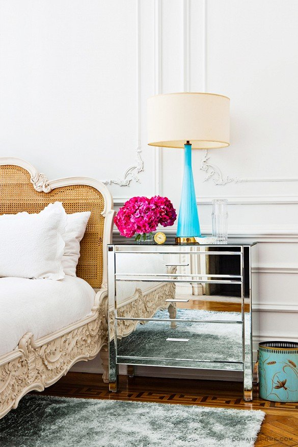 Aqua table lamp on mirrored nightstand next to wicker bed on Thou Swell @thouswellblog