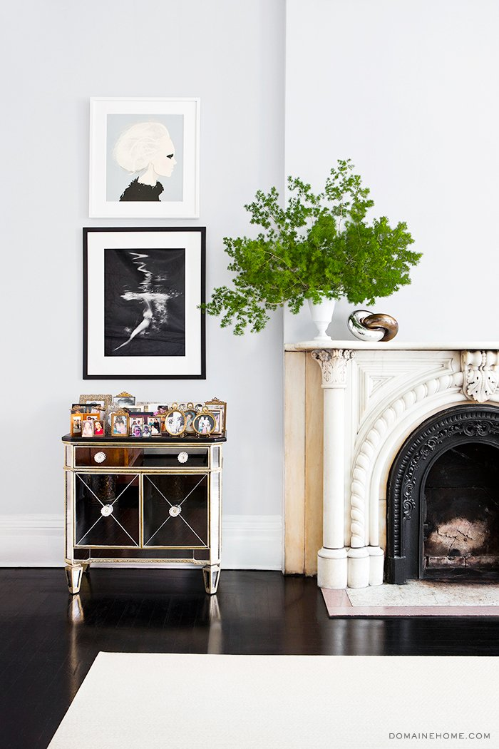 Mirrored table next to ornate fireplace mantel on Thou Swell @thouswellblog