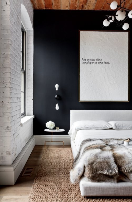 Sleek loft bedroom with platform bed and faux fur throw via @thouswellblog