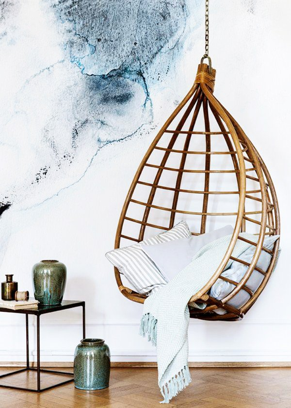 Serene hanging chair stuffed with blue pillows and a blanket.