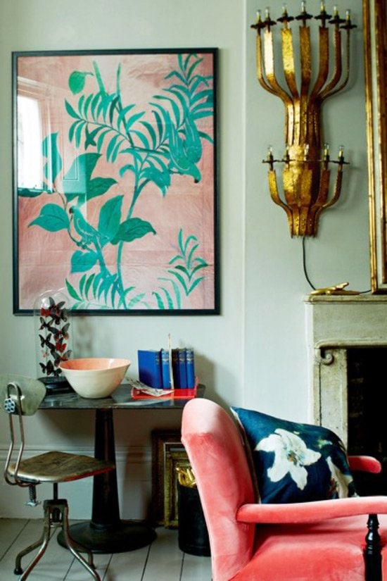 An eclectic living room vignette featuring an oversized gilded sconce and pink velvet armchair.