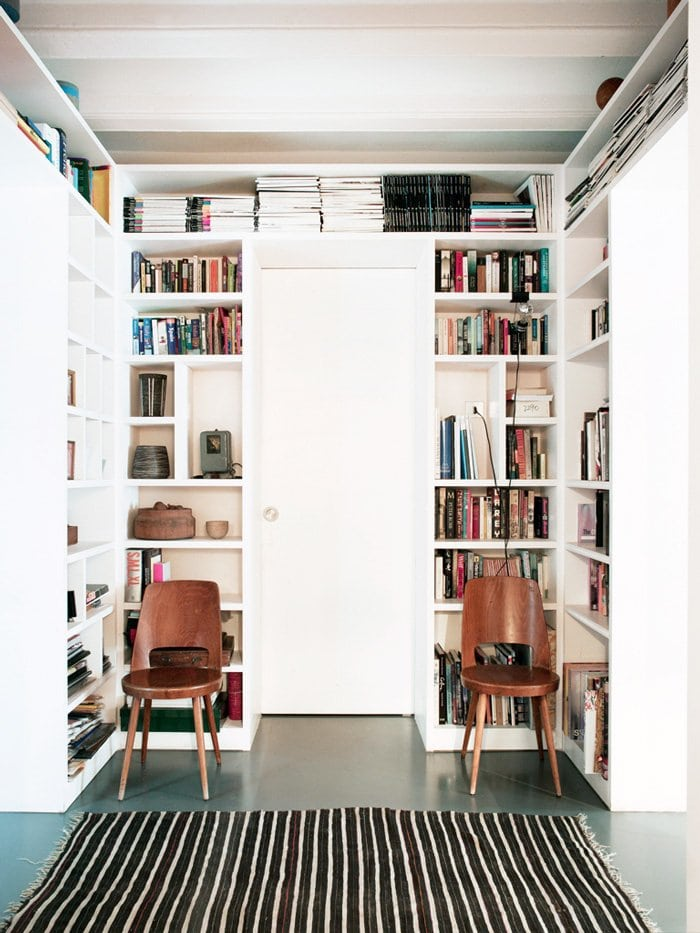Library-style entry with bookshelf-lined walls and simple modern side chairs and striped rug.