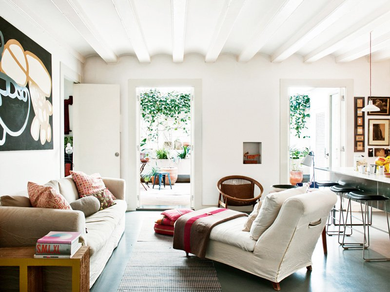 Bright white, comfortable Spanish living room. Exposed beam ceilings, simple upholstered chaise with a garden view.