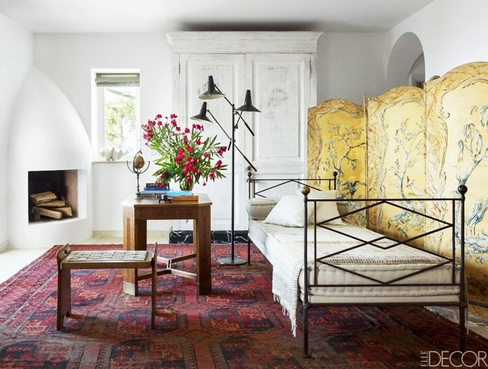 Antique folding screen, persian rug, and daybed in an all white island home on Capri.