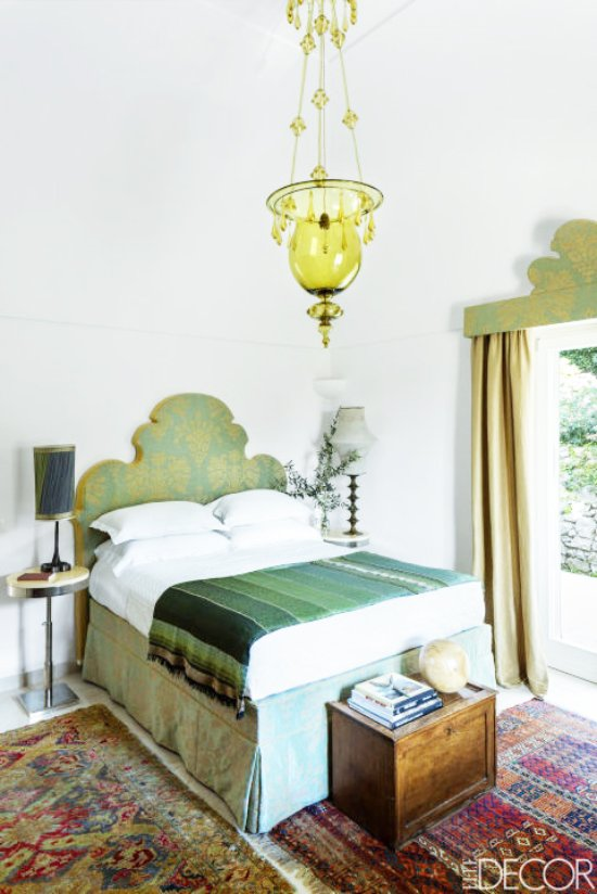 Bright green glass pendant and green silk headboard and bedskirt in a serene island home on Capri.