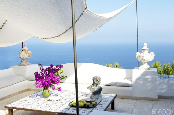 White patio seating area with an infinite view of the ocean in an island home on the coast of Capri.