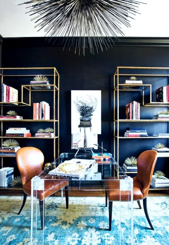 Modern office with lucite desk, leather chairs, and modern metal bookcase