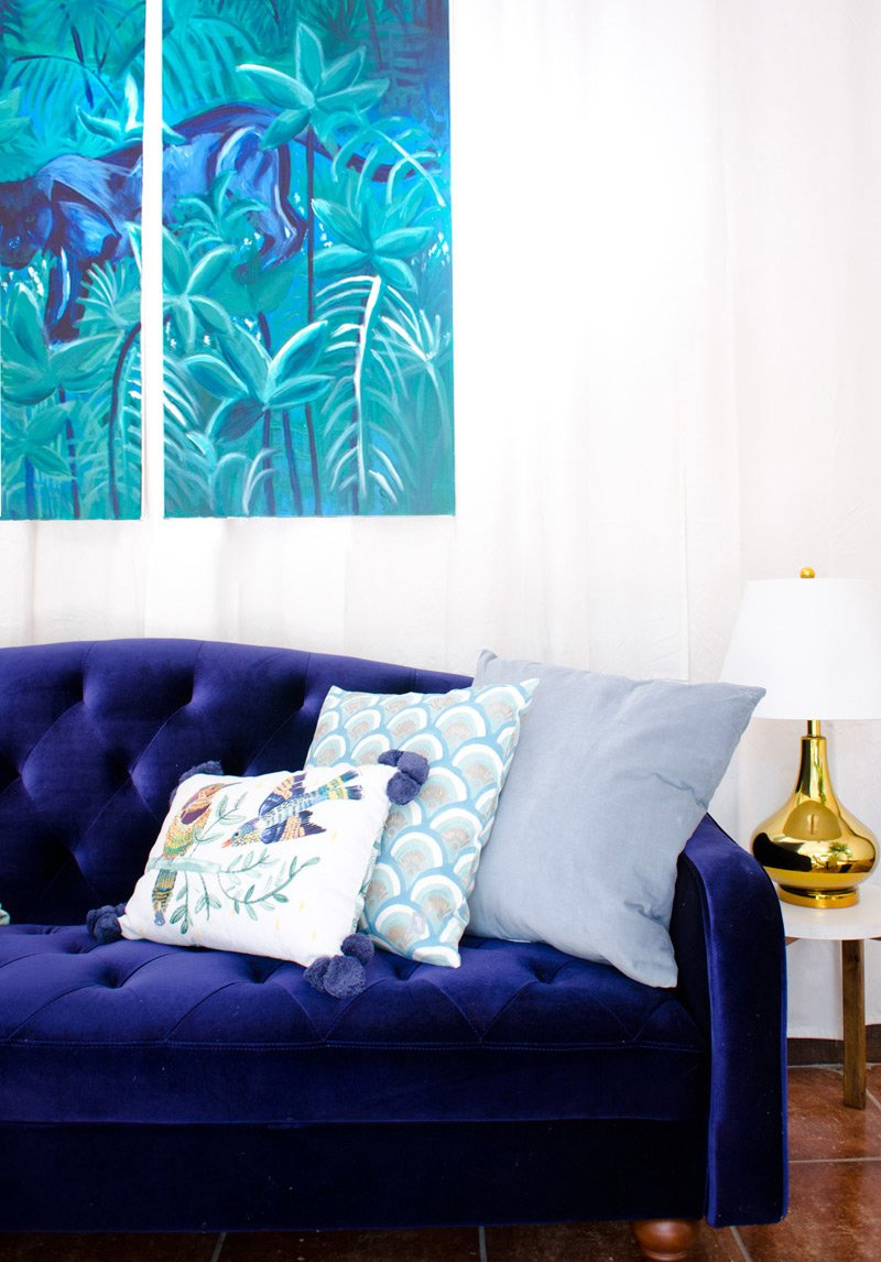 Tufted blue velvet sofa with jungle paintings and gold table lamp.