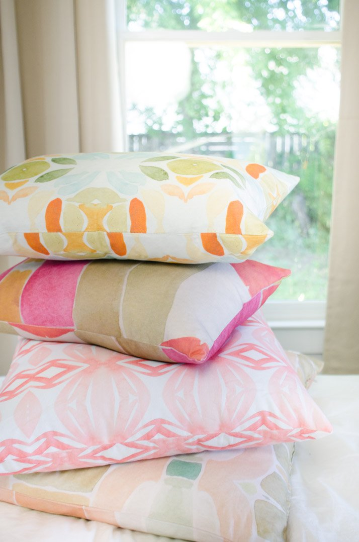 White bedroom with splashes of colorful watercolor patterns from the Bunglo Home Spring pillow collection.