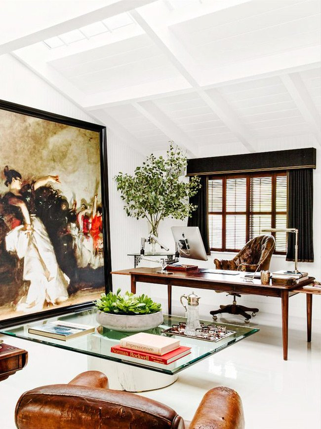 Traditional mix in contemporary loft-like home office with oversized artwork and leather club chairs.