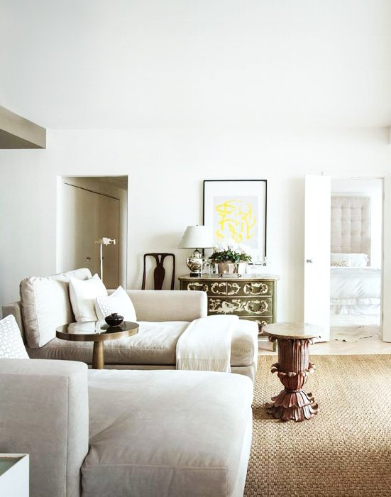 Serene living space with white walls,  linen daybeds, and antique accents in the pied-à-terre of architect Bill Ingram.