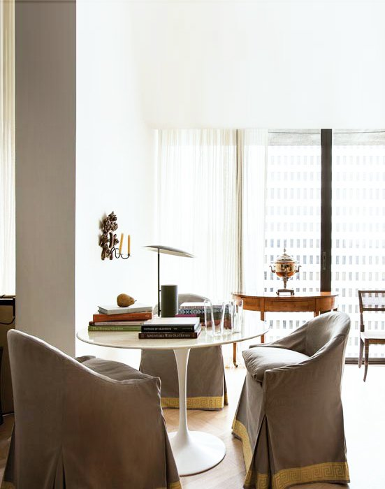A serene and light filled dining space with slip-covered benches and a modern Saarinen table in the pied-à-terre of architect Bill Ingram.