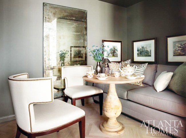 Dramatic grey dining nook with mirror, pedestal table and banquette in the dining room of architect Bill Ingram.