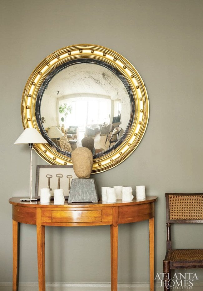 A classic gilt mirror on a brown wall in a vignette in an elegant pied-à-terre.