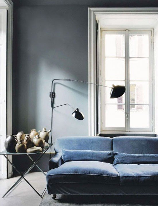 Moody living room vignette with gray walls, blue velvet sofa, and black double swing-arm wall sconce.