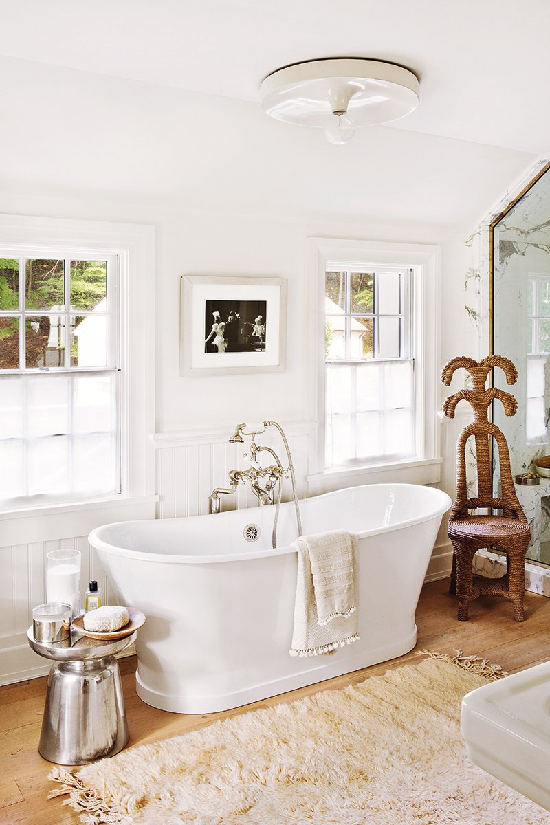 Elegant white bathroom with beautiful tub in a modern farmhouse renovation via @thouswellblog