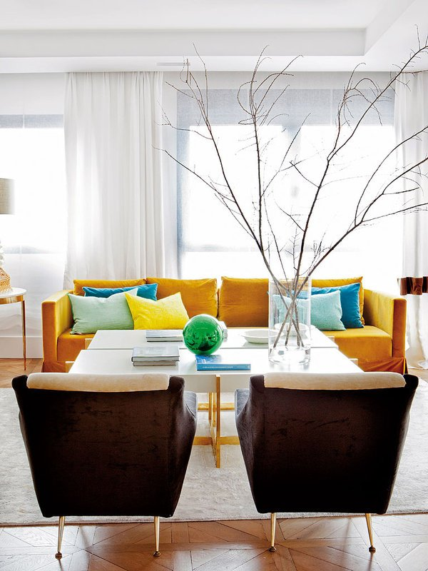 A colorful sofa adds a focal point to the white living room in a Spanish flat.