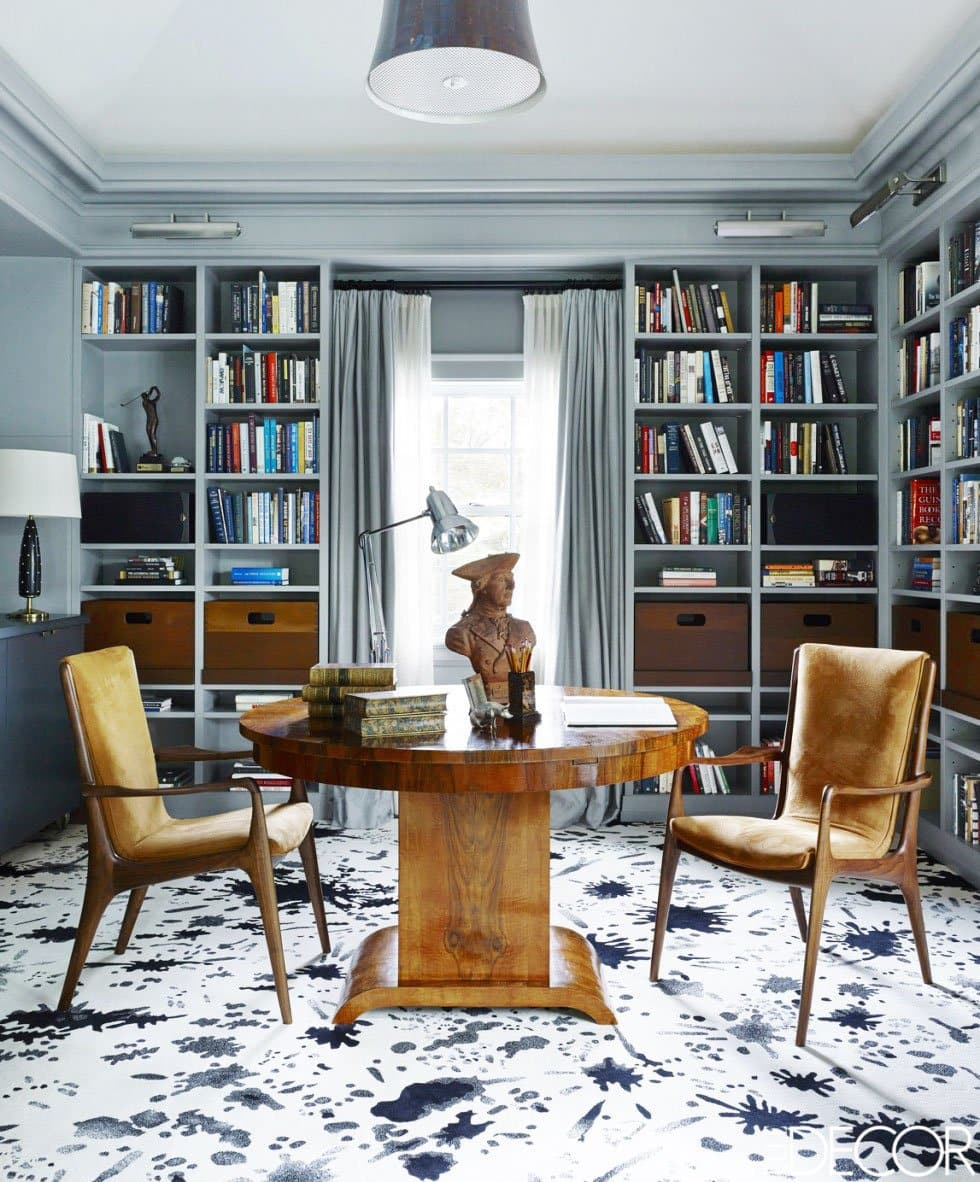 A modern and moody office study with mid-century chairs and an antique pedestal table.