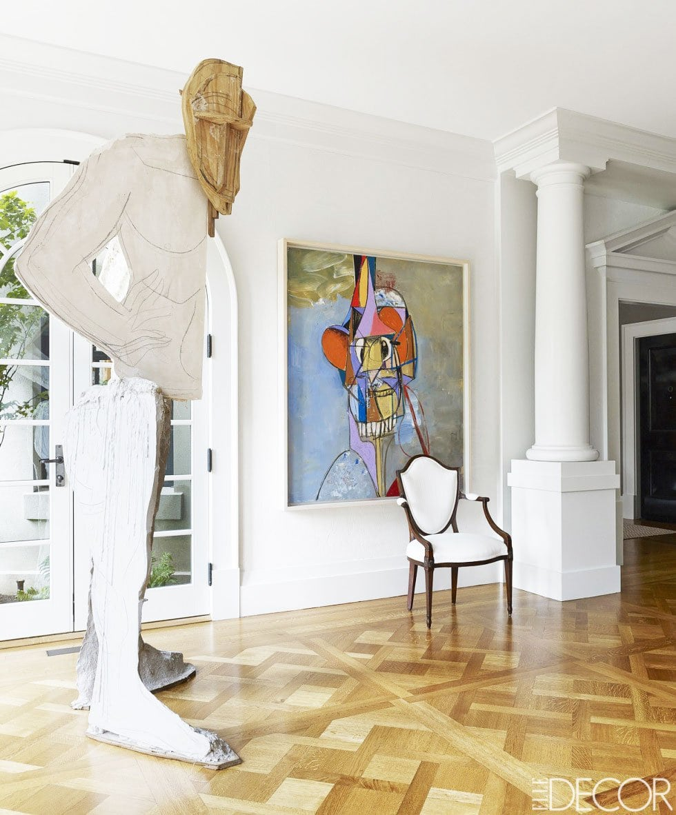 An all white art-filled entry in a sophisticated Toronto home.