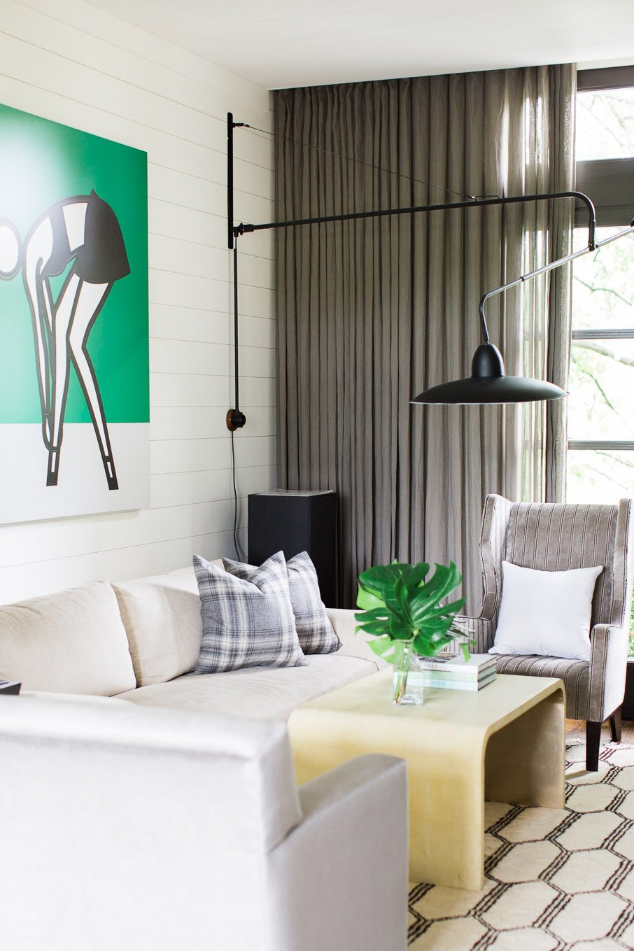 A neutral living room with comfortable seating and a pop of modern art on @thouswellblog