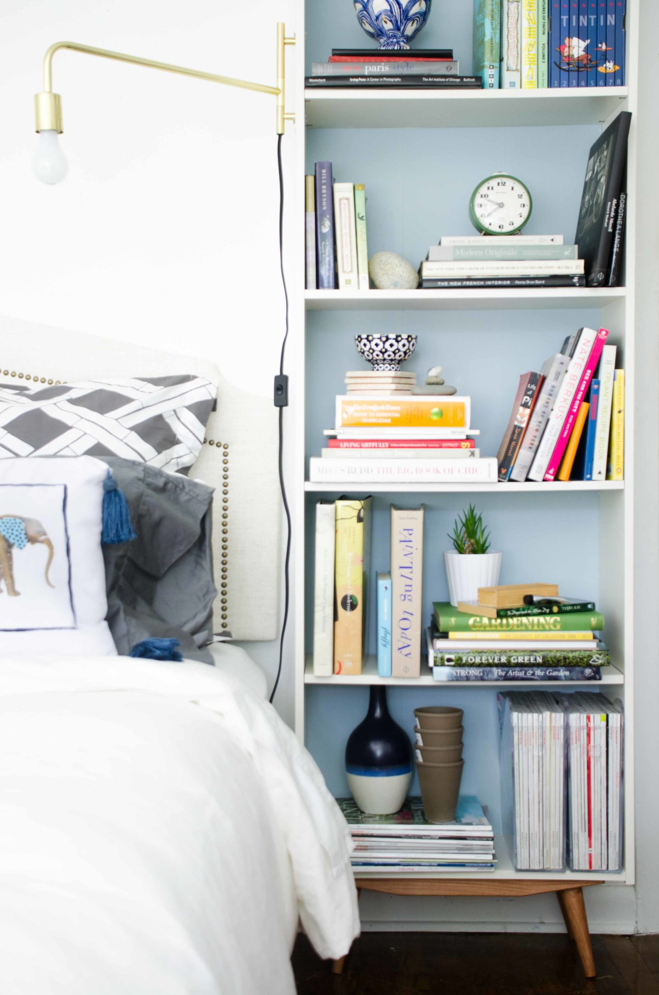 Mid-century bookcase with brass swing-arm sconce in a modern bedroom.