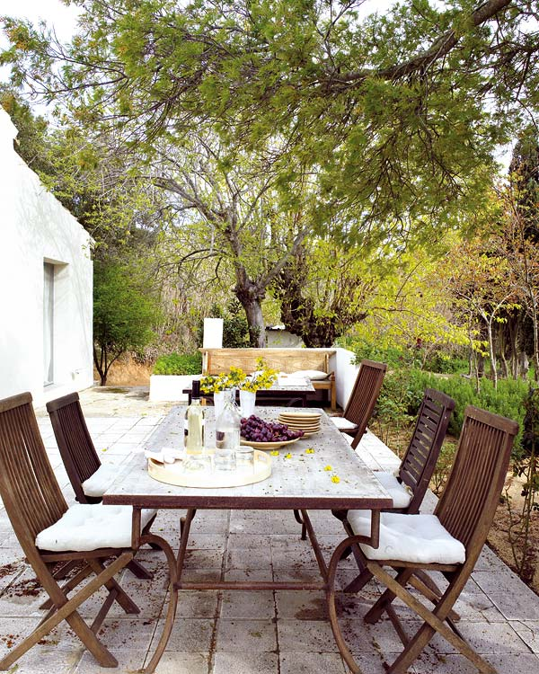 A shade-covered patio dining area with teak table and chairs.