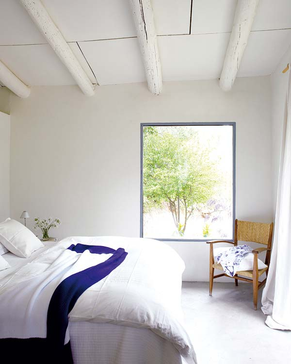 A simple, laid-back country home bedroom in all white.