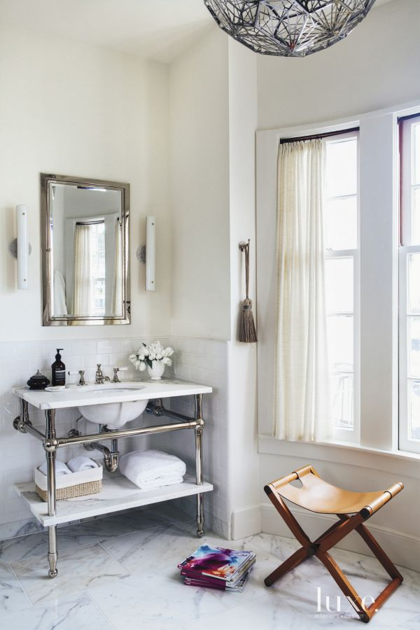 An elegant white and silver bathroom with a leather stool.