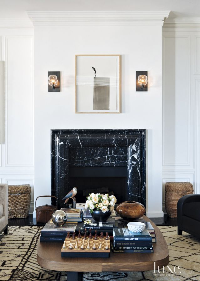 A modern black marble fireplace in a sleek living room.