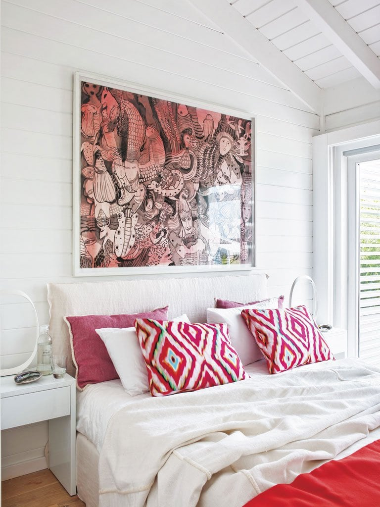 Pops of pink in the wall art and pillows add life to a simple beach bedroom in Portugal.