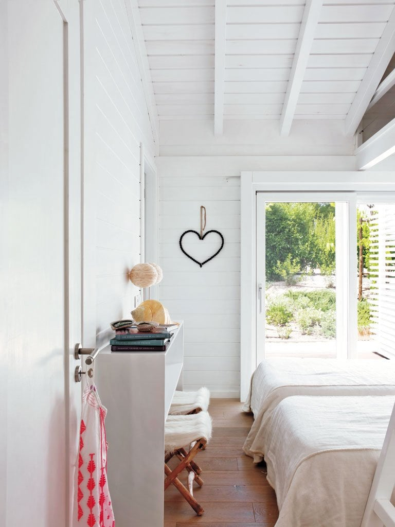 A simple white bedroom with heart wall decor and large windows.