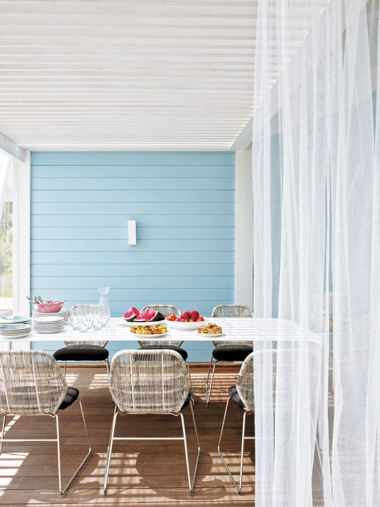 A serene porch dining area in white and blue in a home in Portugal.