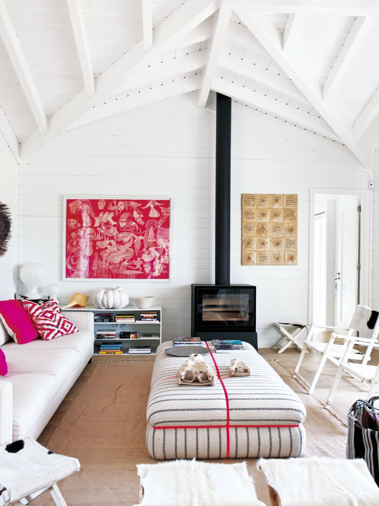 A bright modern living room with pops of pink in a home in Portugal.