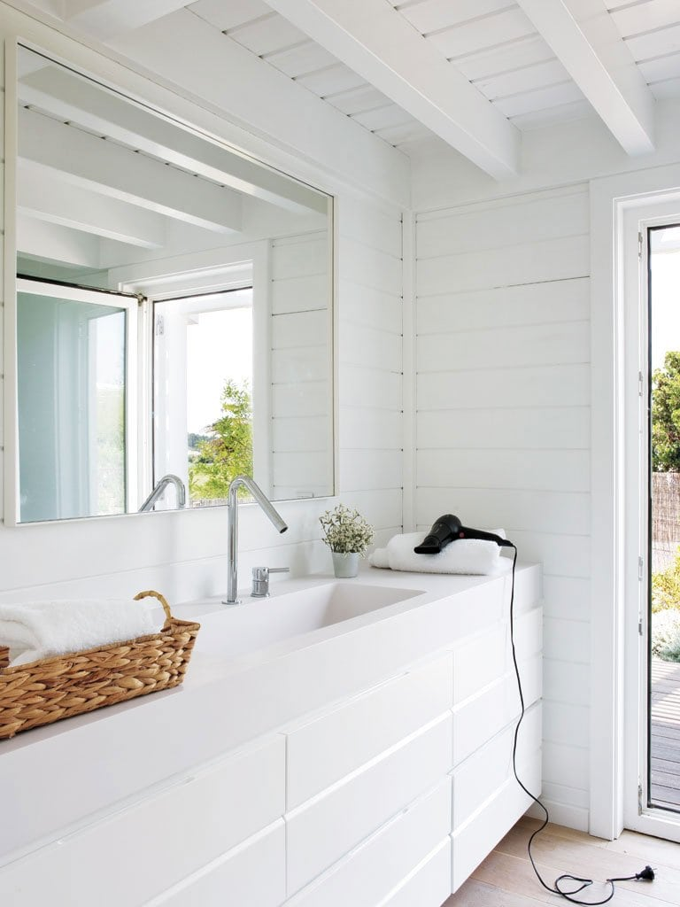 A serene modern bathroom in all white with a sleek vanity.