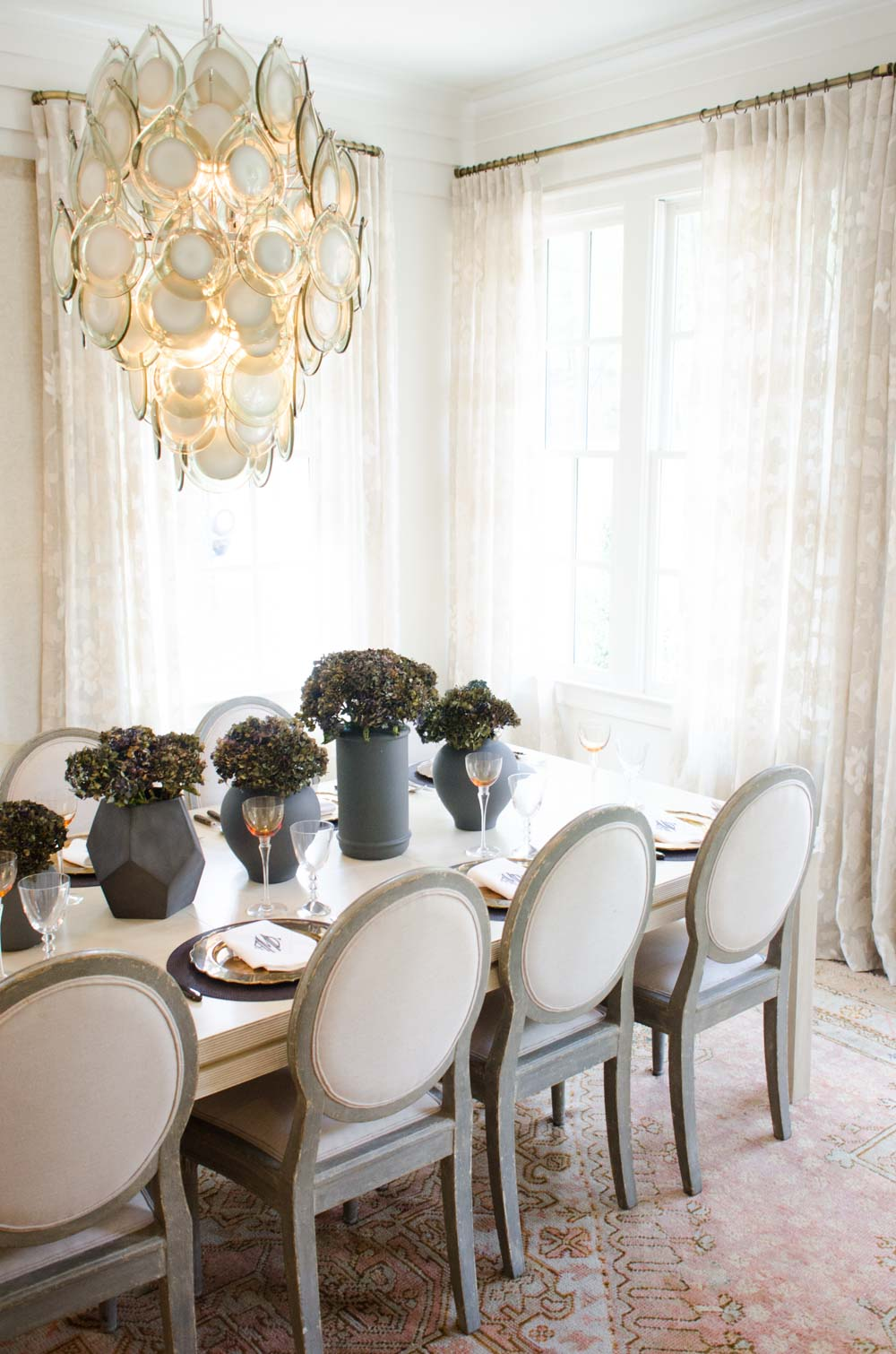 Bright serene dining room with shell chandelier