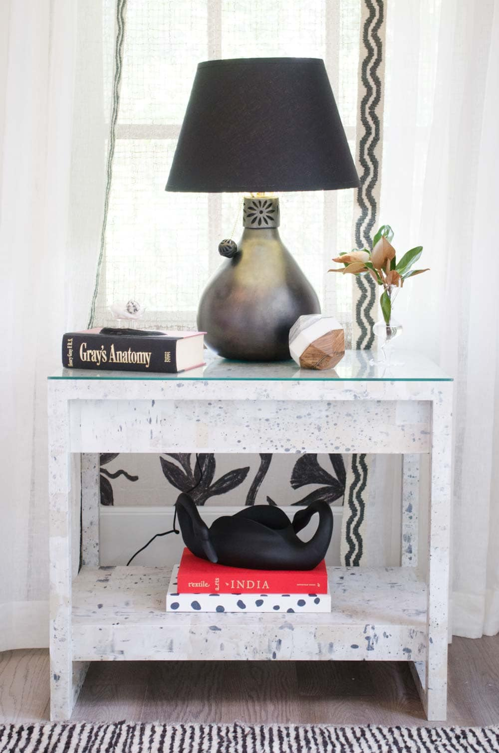Bright white bedroom with painted wallpaper and black table lamp