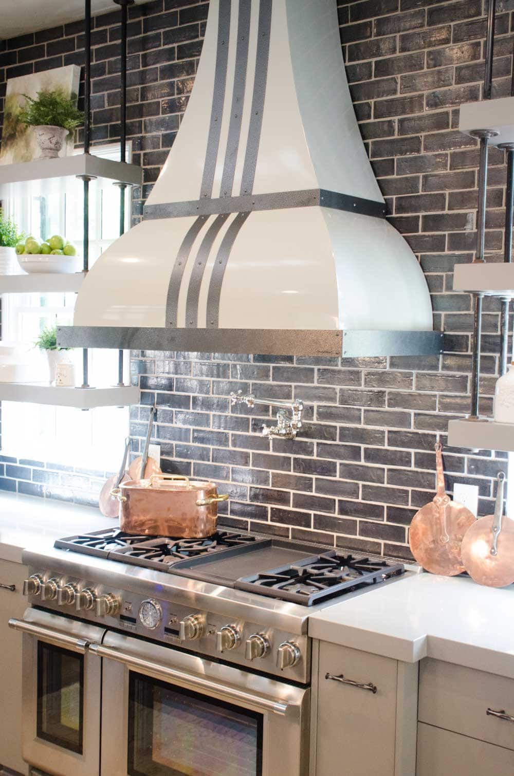 Kitchen design with gray subway tiles and striped range hood
