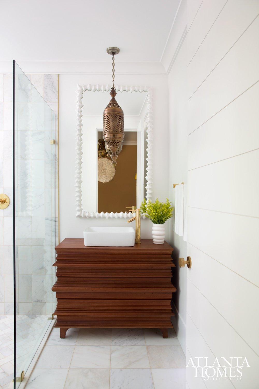 Elegant white bathroom with worldly lantern pendant and modern wood vanity.
