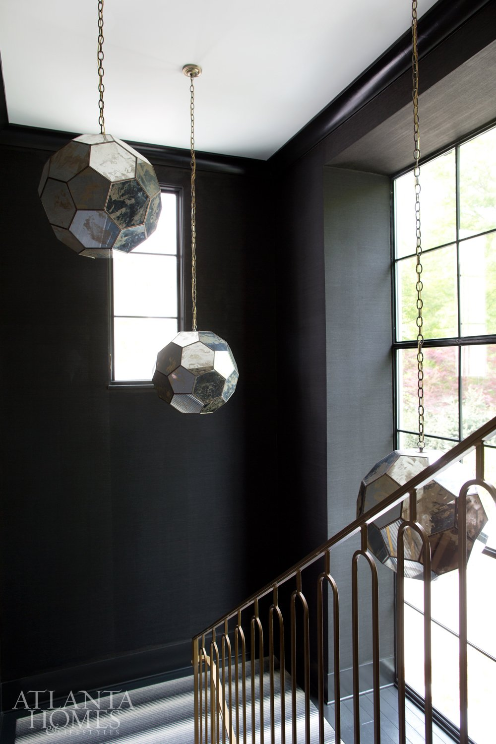Modern black staircase with faceted pendant lamps.