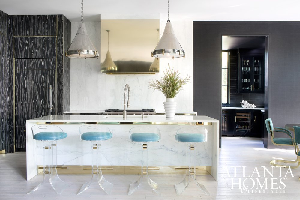 Modern kitchen with aqua lucite stools, marble island, and brass range hood.