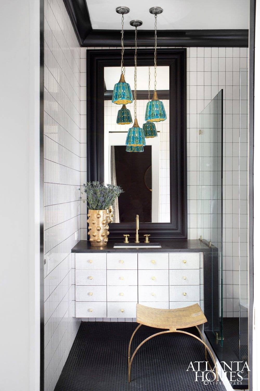 White tile bathroom with aqua pendants.