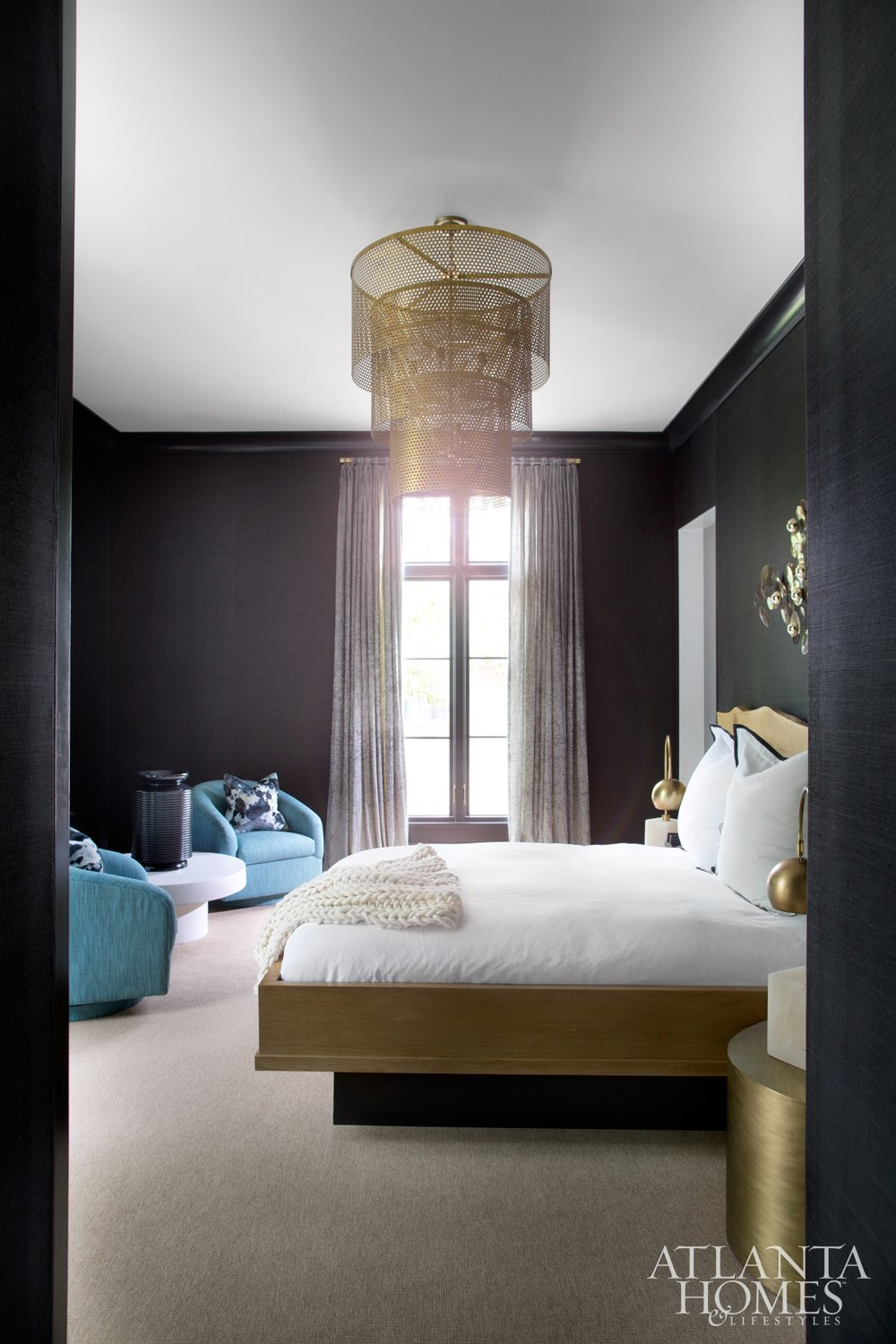 Modern bedroom with black walls and aqua mid-century chairs and gold chandelier.