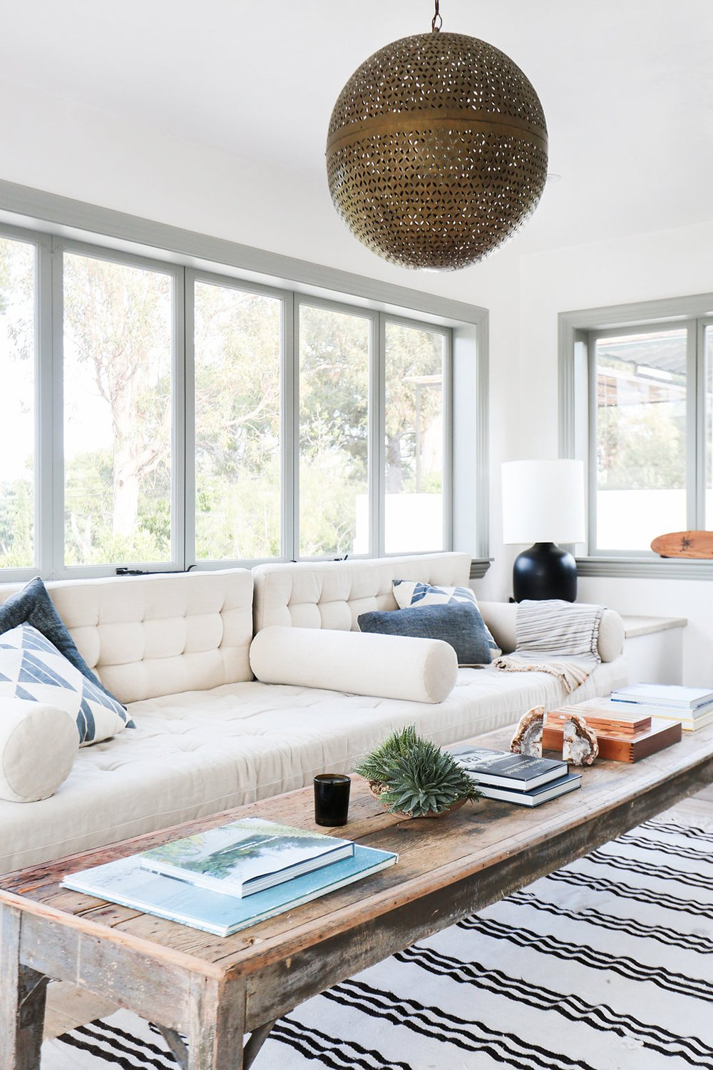 Modern easy-going California living room with a pale tufted sofa and gold pendant light.