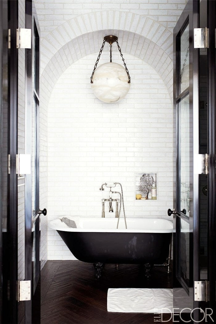 The moody black and white bathroom with free-standing tub in Johnny Buckland's Manhattan pad.