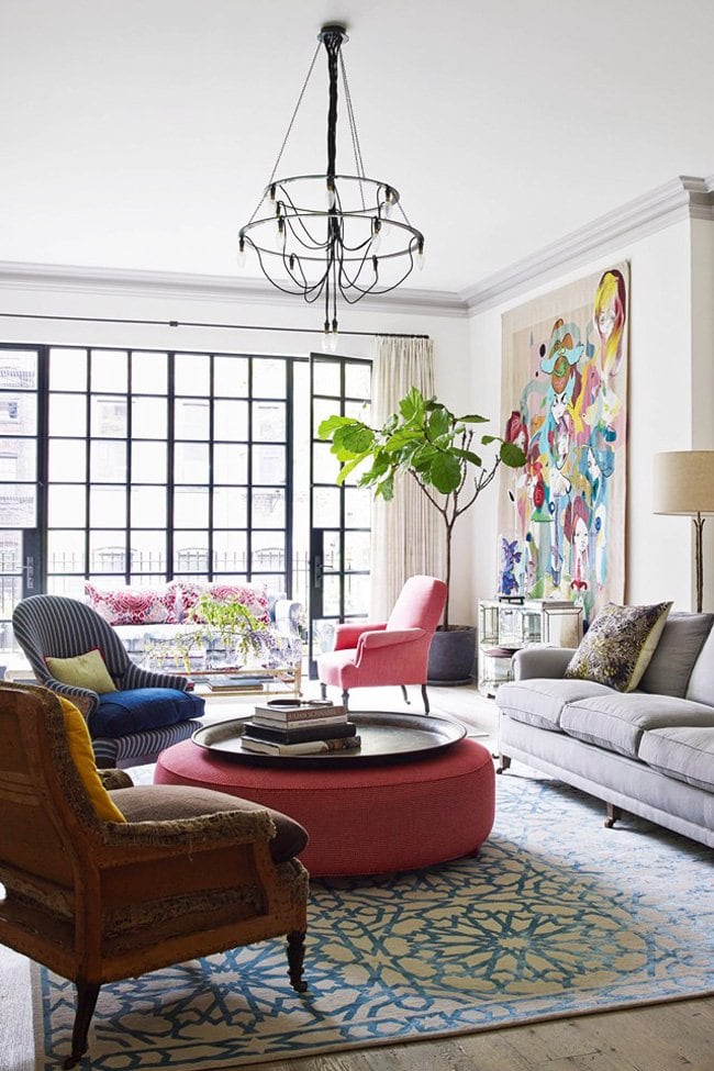 Bright, colorful West Village living room with blue rug, pink ottoman, oversized art, and a fiddle-leaf fig.