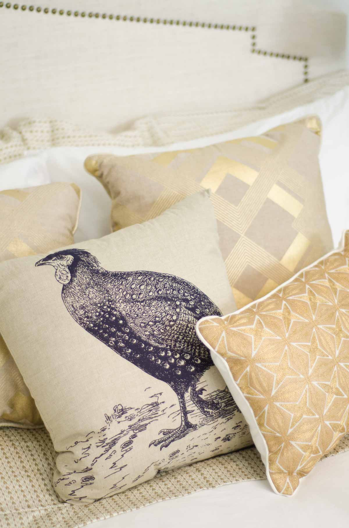 Gold throw pillows on a white bed on @thouswellblog