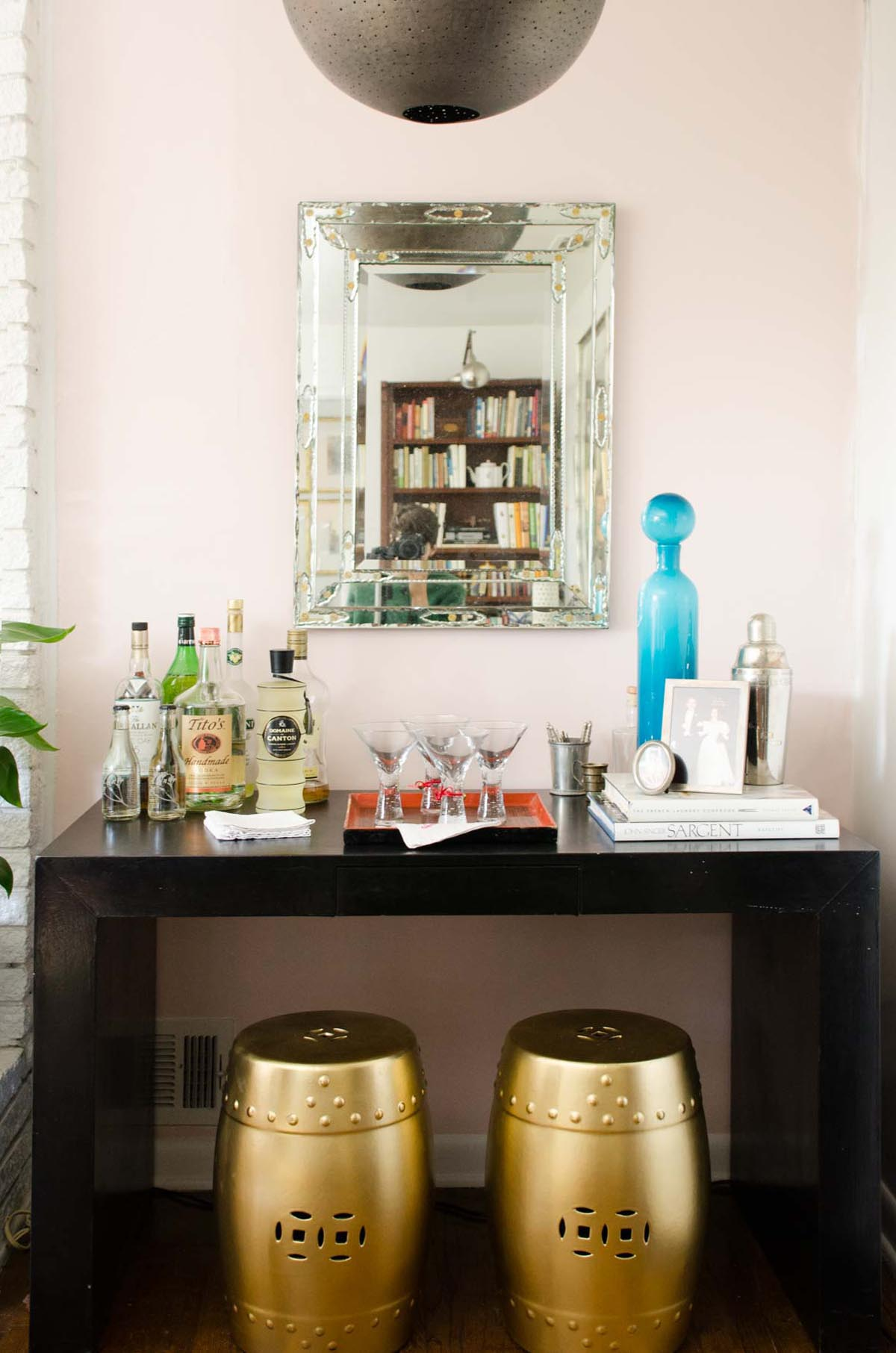 Black parsons table bar with pink accent wall and gold garden stools on @thouswellblog