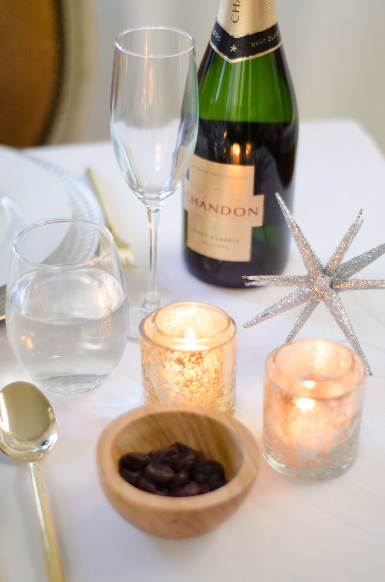Glowing candles in an elegant silver and gold holiday table setting on @thouswellblog