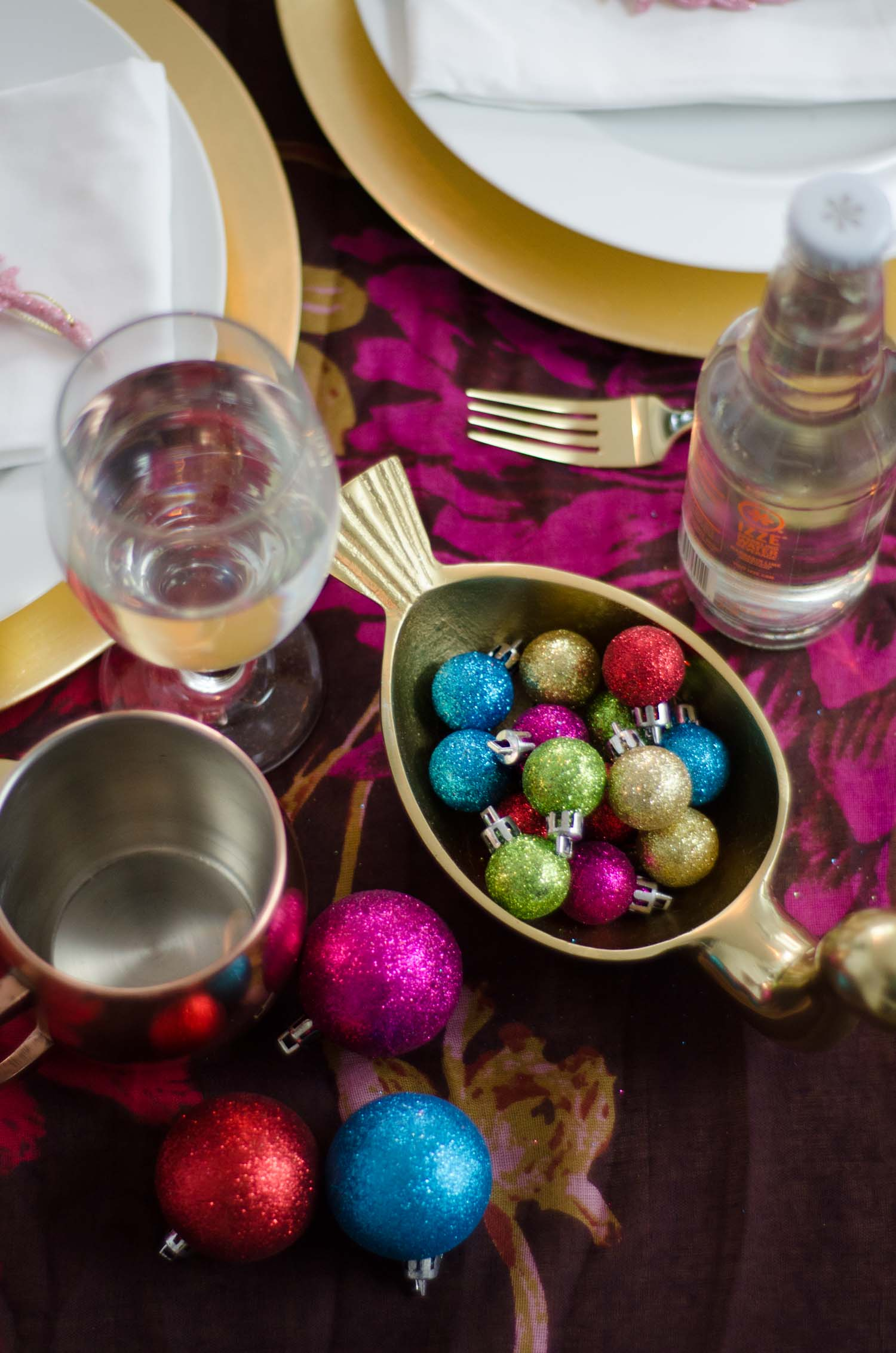 Sparkly Christmas ornaments in holiday brights in a Nate Berkus bird dish, vibrant holiday table setting on @thouswellblog